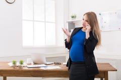 怀孕的女商人谈话在电话在办公室 库存图片