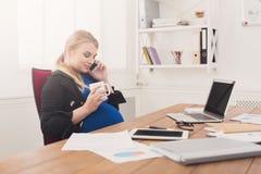怀孕的女商人谈话在电话在办公室 免版税库存图片