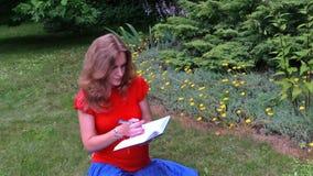 怀孕的女孩写日志在美丽的sucullent庭院坐 免版税库存图片