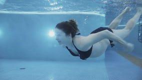 怀孕的女孩在水池潜水 股票视频