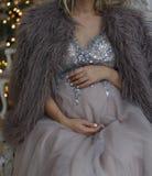 怀孕的女孩坐在一件蓝色礼服的长沙发有闪闪发光的 免版税图库摄影