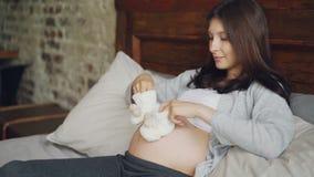 怀孕的女孩爱恋的母亲在她的大腹部上把童鞋放并且走他们在使用与未来的婴孩爆沸 影视素材