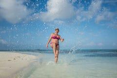 怀孕的女孩踢在海滩的水 库存图片