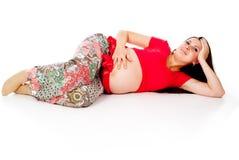 怀孕的女孩,谎言 免版税图库摄影