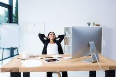 怀孕的女实业家放松的和听的音乐在办公室用手 库存照片