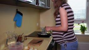 怀孕的女性厨师食物在烹调在滚刀的厨房里平底锅 股票录像