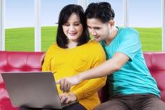 怀孕的女性和丈夫有膝上型计算机的 免版税库存照片