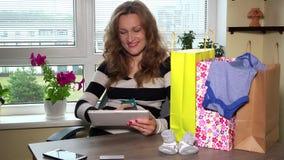 怀孕的女性在木桌上的购物网上网站和许多购物袋 影视素材