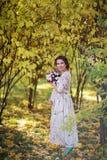 怀孕的女性在秋天 免版税库存照片