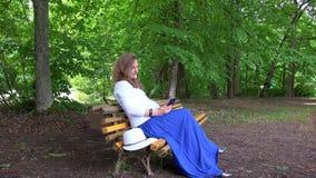 怀孕的女性浏览与智能手机坐公园长椅 股票录像