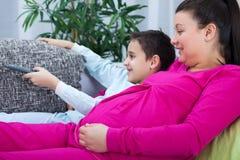 怀孕的妈妈和儿子观看的电视一起 免版税库存照片