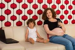 怀孕的妈妈和小孩男孩家 免版税库存图片