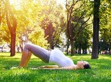 怀孕的少妇实践的瑜伽锻炼在公园 库存图片