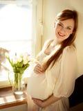 怀孕的微笑的妇女 库存照片