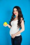 怀孕的愉快的少妇用在蓝色背景的绿色苹果, 免版税库存照片