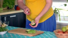 怀孕的房子在家剥落鲕梨果子的妻子腹部和手在厨房里 股票录像