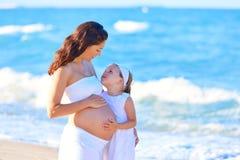 怀孕的母亲和女儿海滩的 免版税库存图片