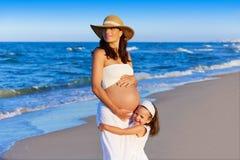 怀孕的母亲和女儿海滩的 库存图片