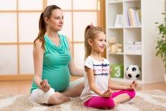 怀孕的母亲和孩子在莲花做瑜伽,放松 库存图片