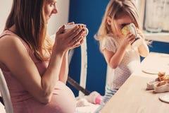 怀孕的母亲和食用早餐和喝茶的女婴生活方式捕获在家 库存照片