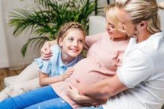 怀孕的母亲的父亲和女儿感人的腹部,当坐时 免版税库存图片
