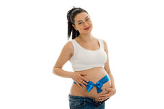 怀孕的浅黑肤色的男人画象白色衬衣的有在她的看和微笑在照相机的腹部的蓝色磁带的隔绝在白色 免版税图库摄影