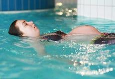 怀孕的游泳妇女 库存照片
