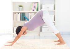 怀孕的瑜伽在家 免版税库存图片