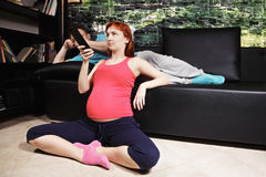 怀孕的电视注意的妇女 图库摄影