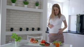 怀孕的维生素食物,有大肚子跳舞的可爱的未来母亲在早午餐时间的厨房与新鲜蔬菜 股票录像