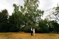 怀孕的美丽的妇女和她英俊的丈夫可爱放松在自然,有野餐在秋天公园 库存照片