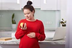 怀孕的美女藏品苹果在手中 可爱的未来母亲感到轻松,并且愉快,迷人的妇女有身体好, 免版税库存照片