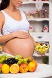 怀孕的肚子的特写镜头用沙拉新鲜水果和板材  健康怀孕、饮食和维生素 库存图片