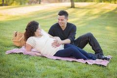 怀孕的西班牙夫妇在户外公园 免版税库存图片