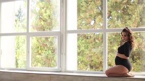 怀孕的moman在大窗口前面坐 在黑紧身衣裤穿戴的模型 她在腹部上把她的手放 愉快的远期 股票视频
