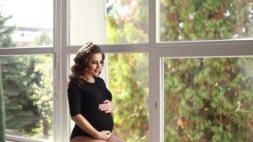 怀孕的moman在大窗口前面坐 在黑紧身衣裤穿戴的模型 她在腹部上把她的手放 愉快的远期 股票录像