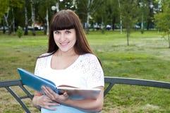 怀孕美丽的书的公园读了妇女 库存照片