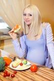 怀孕美丽的金发碧眼的女人和健康食物 库存照片