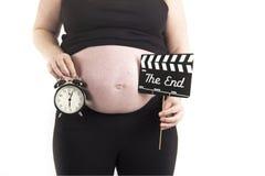 怀孕腹部的时钟 免版税库存照片