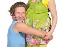 怀孕1个腹部拥抱的人 免版税库存图片