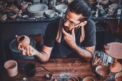 怀疑人看他自己的工作,陶瓷茶壶 库存图片
