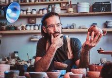 怀疑人看他自己的工作,陶瓷茶壶 免版税图库摄影