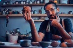 怀疑人看他自己的工作,陶瓷茶壶 免版税库存照片