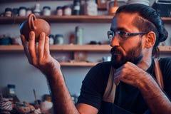 怀疑人看他自己的工作,陶瓷茶壶 图库摄影