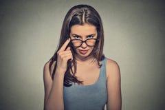 戴怀疑地看您的眼镜的恼怒的坏心眼的严肃的妇女 库存图片