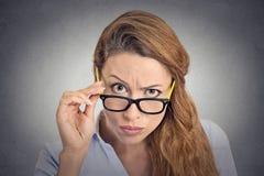戴怀疑地看您的眼镜的特写恼怒的坏心眼的妇女 库存图片