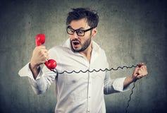 怀疑地看电话机的愤懑震惊人 免版税图库摄影