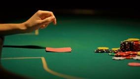 怀疑,但是把金钱放的妇女在啤牌桌,希望上赢得,赌博的运气 影视素材