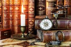 怀表、燃烧的蜡烛和旧书 库存图片