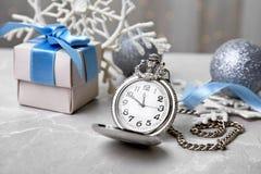 怀表、礼物和欢乐装饰在桌上 免版税库存照片